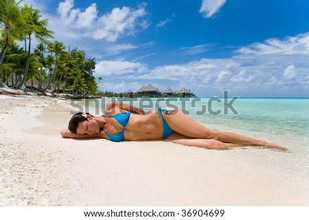 woman on tropical beach at resort with palm tree and bungalows