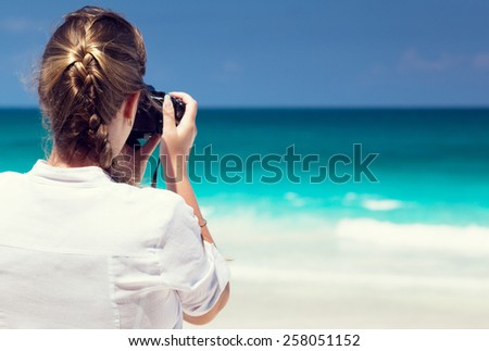 woman on tropical beach taking photo with mirrorless camera - stock photo