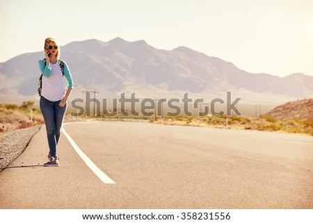 Woman On Vacation Hitchhiking Along Road Using Mobile Phone - stock photo