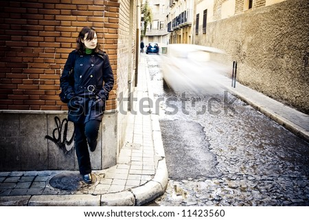 Woman on wall in urban background. - stock photo