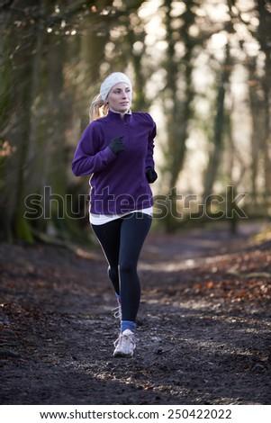 Woman On Winter Run Through Woodland - stock photo