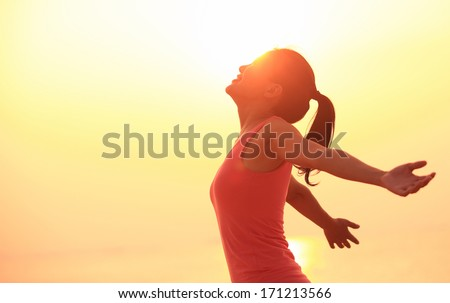 woman open arms under the sunrise at sea  - stock photo