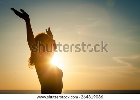 woman open arms under the sunset at sea - stock photo