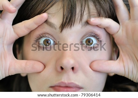 woman opened eyes with your fingers - stock photo