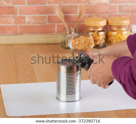 woman opening a can of corn with can opener in the kitchen - stock photo