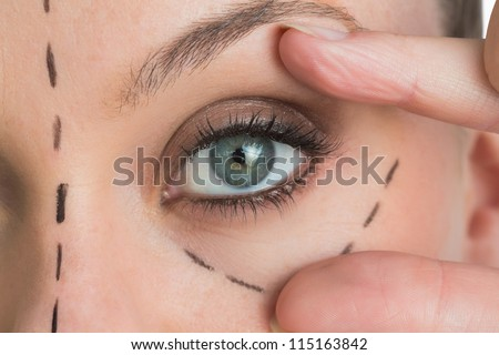 Woman opening the green eye with her hand in the white background