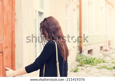 woman opens the door outside portrait - stock photo