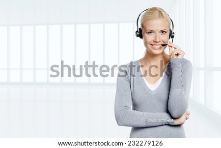 Woman-operator speaking on the microphone of the earphone in office - stock photo