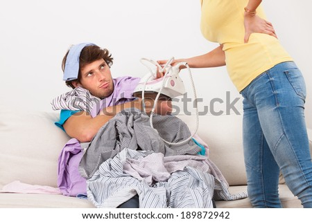 Woman ordering lazy man to ironing his clothes - stock photo
