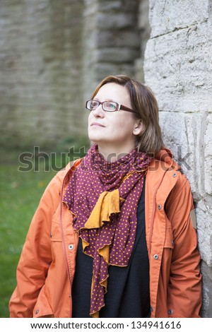 Woman outdoor, leaning towards a stone wall looking up to camera left with a calm, contemplating expression. - stock photo