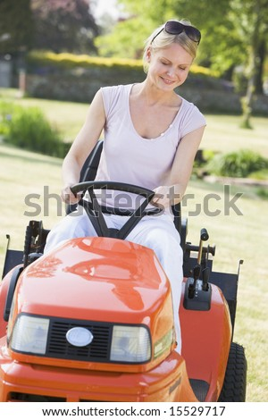 Woman outdoors driving lawnmower smiling - stock photo