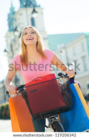 Woman outdoors on bicycle with shopping bags - stock photo