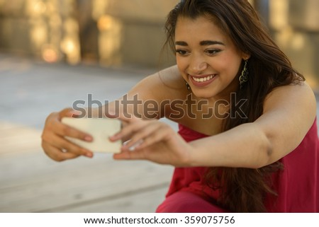 Woman outdoors taking selfie picture with mobile phone