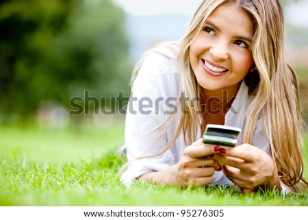 Woman outdoors texting on her mobile phone - stock photo