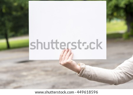 woman outdoors with blank white card