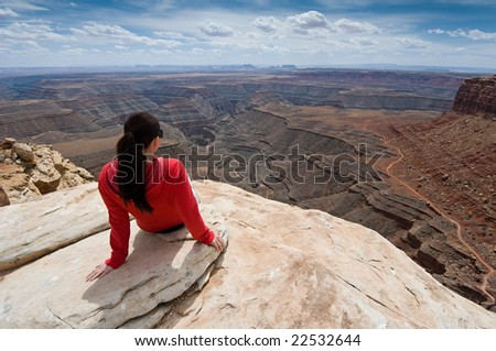 Woman overlooking Goosenecks State Park and Monument Valley, Utah, from Muley Point - stock photo