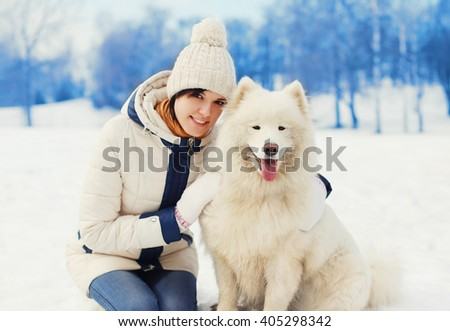 Woman owner hugging white Samoyed dog on snow in winter day - stock photo