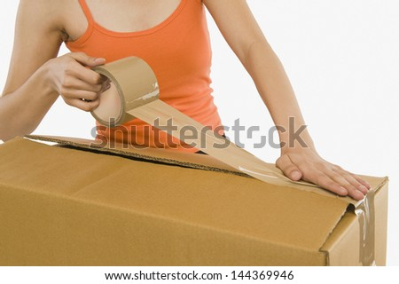 Woman packing cardboard by packing tape - stock photo