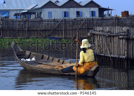 Woman paddling a dugout canoe through a floating village in Siem Reap during the rainy season