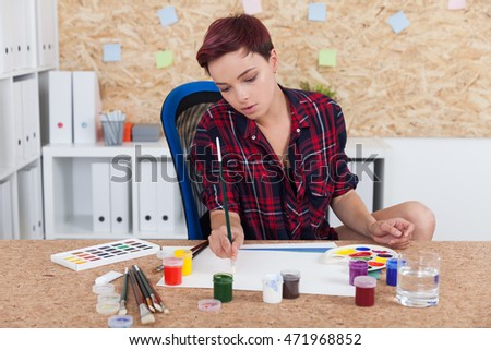 Woman painter at work in college office. Cork board on wall. Palette and paint lie on desk. Concept of higher education in art and sculpture.