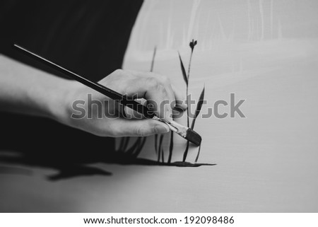 woman painter hand painting in her studio on canvas. black and white - stock photo