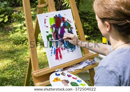 woman painting at a canvas with palette knife