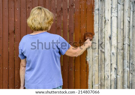 Woman Painting Cedar Color Stain on Old White Fence - stock photo
