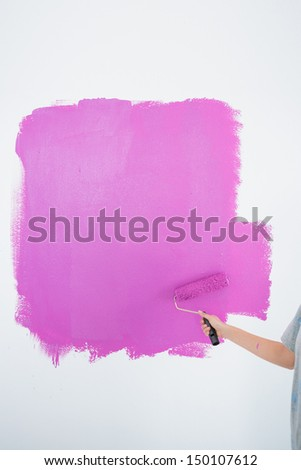 Woman painting her wall pink in a new home