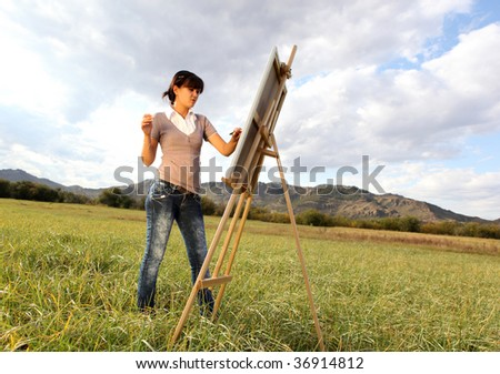 Woman painting landscape - stock photo