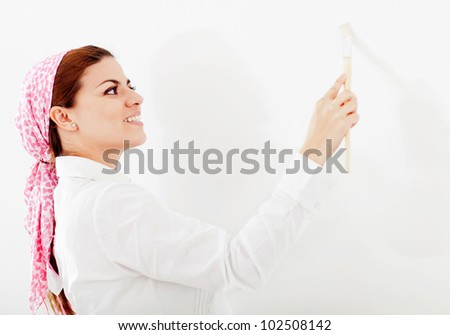 Woman painting the walls of her house - stock photo