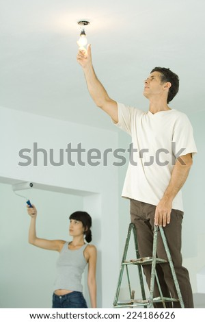 Woman painting with paint roller, man changing light bulb - stock photo
