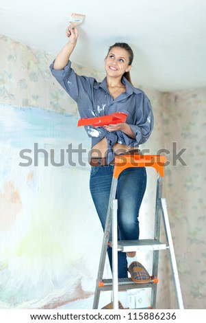 Woman paints ceiling with brush at home - stock photo