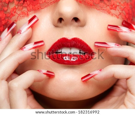Woman part of face with eyes closed by red ribbon and with red french acrylic nails manicure - stock photo