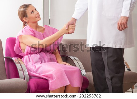 Woman patient in 40s shaking hand with doctor in hospital waiting room before checkup. - stock photo