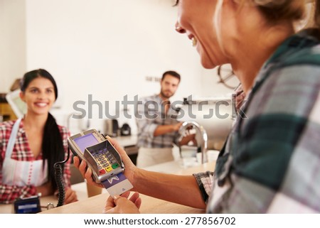 Woman paying by credit card in a cafe - stock photo