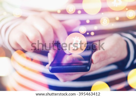 Woman paying with Bitcoins over smartphone, close up of female hands using mobile phone device to complete online transaction, collecting bitcoins, nice bokeh, selective focus. - stock photo
