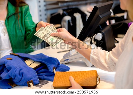 woman paying with dollars in the clothes shop over the counter - stock photo