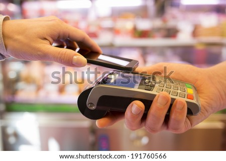 Woman paying with NFC technology on mobile phone, in supermarket  - stock photo