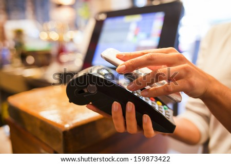 Woman paying with NFC technology on mobile phone, restaurant, cafe, bar - stock photo