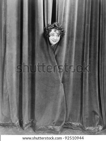 Woman peek-a-booing behind a curtain - stock photo