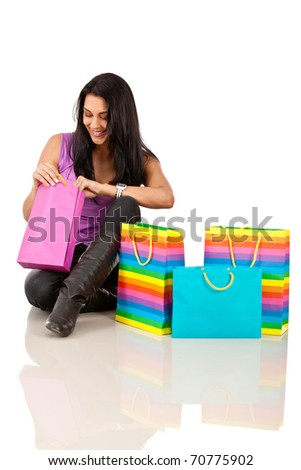 Woman peeking into shopping bags - isolated over white