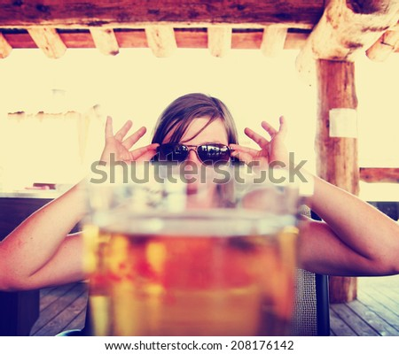 woman peeking over a fresh draft beer as her drink toned with a vintage retro style instagram filter - stock photo