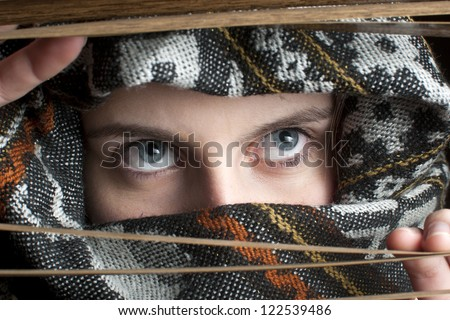 Woman peeking through blinds  - stock photo