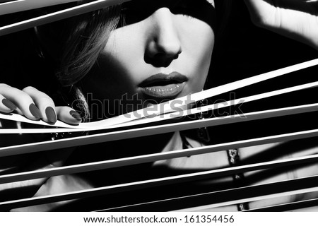 Woman peeking through the jalousie - stock photo