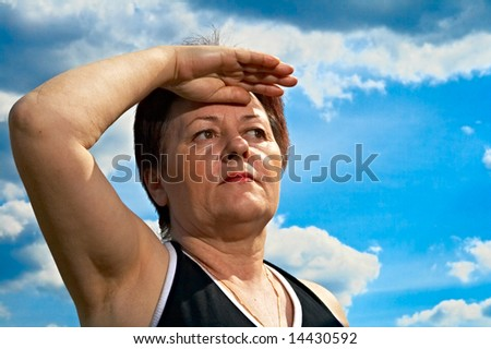 woman peers into distance on background blue sky