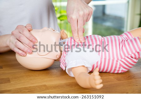woman performing CPR on baby training doll with one hand compression - stock photo