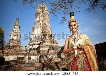 woman performing typical thai dance with thai style temple background, identity culture of thailand - stock photo