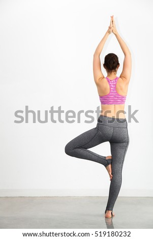 Woman Performing Yoga Pose Over White Background On Gray Floor In Home  Studio   Pilates,