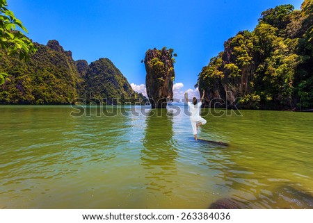 Woman performs yoga pose standing in the water of the Andaman Sea. Exotic vacation in Thailand - stock photo