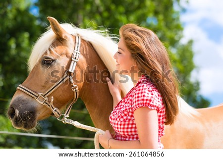 Woman petting horse on pony farm